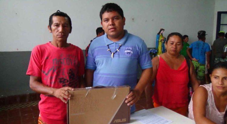 Imagem: Diretor da FOIRN de referência à região do Médio e Baixo Rio Negro entrega notebook ao líder da comunidade Canafé. Foto: SETCOM/FOIRN