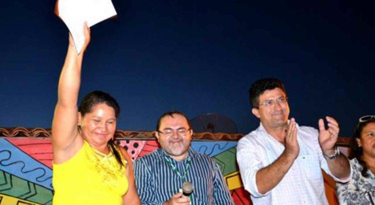Líder quilombola Ana Moreira ergue cópia de Decreto Presidencial para comemorar assinatura - Foto: Ascom Incra/CE